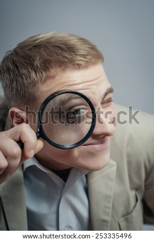 portrait of young man looking through a magnifying glass over grey background