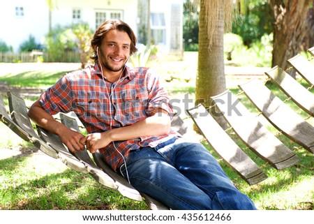 Portrait of young man lying in hammock with earphones - stock photo