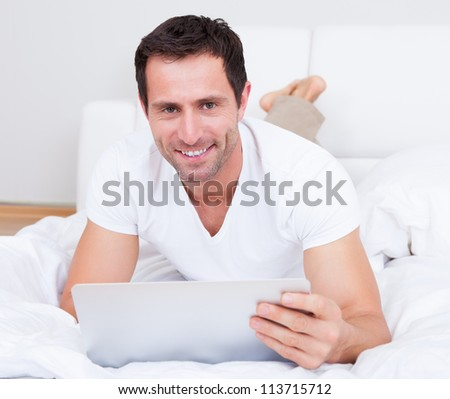 Portrait Of Young Man Lying On Bed Using Laptop, Indoors - stock photo
