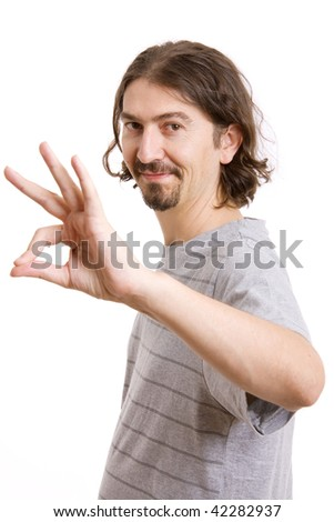 Portrait of young man making ok sign, isolated on white