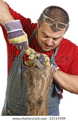 portrait of young man making sculpture from wood - stock photo