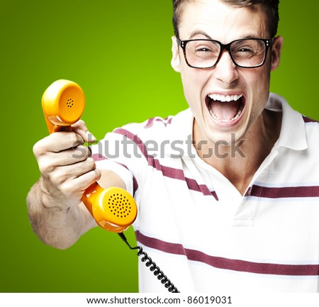 portrait of young man offering vintage telephone to call over green background