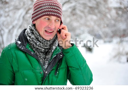 Portrait of young man outdoor in winter park wearing bright clothes speaking phone
