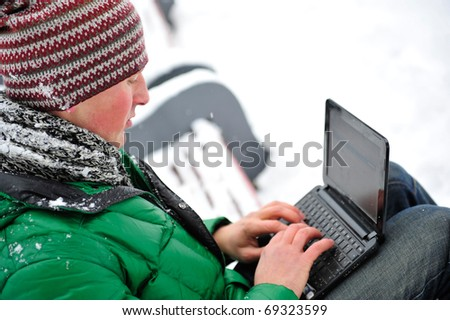 Portrait of young man outdoor in winter park wearing bright clothes working with his netbook and enjoying free wireless internet connection