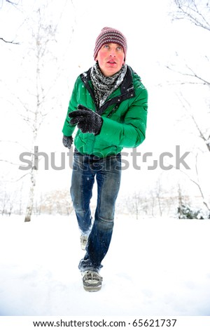 Portrait of young man outdoor running at winter park - stock photo
