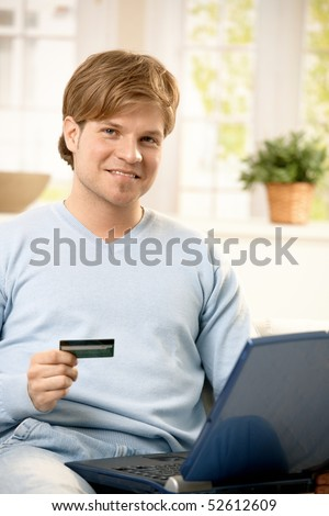 Portrait of young man paying with credit card online, holding computer, smiling at camera. - stock photo
