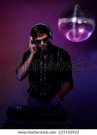 Portrait Of Young Man Playing Dj In Disco