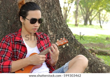 Portrait of young man playing ukulele in public outdoor park.