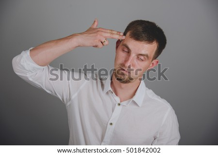 Portrait of young man pointing finger gun gesture to head