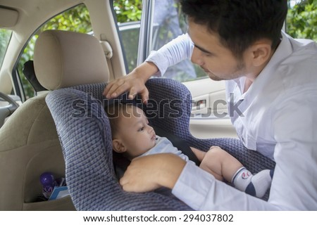 Portrait of young man putting his newborn baby on the car seat - stock photo