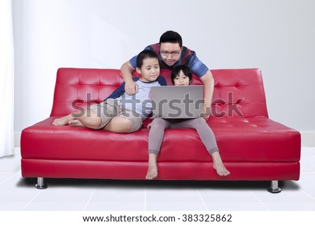 Portrait of young man relaxing at home with his children while using laptop computer on the sofa - stock photo