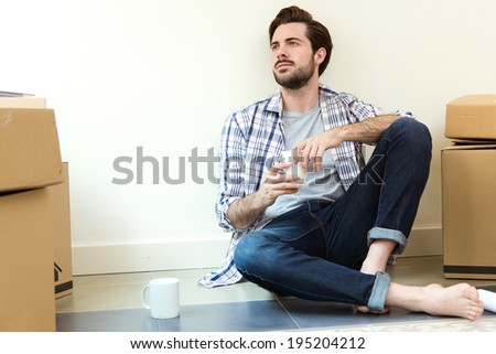 Portrait of Young man resting during the move to their new home - stock photo