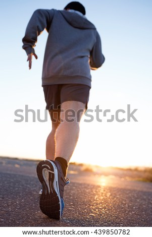 Portrait of young man running in the street.