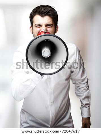 portrait of young man screaming with megaphone against a abstract background
