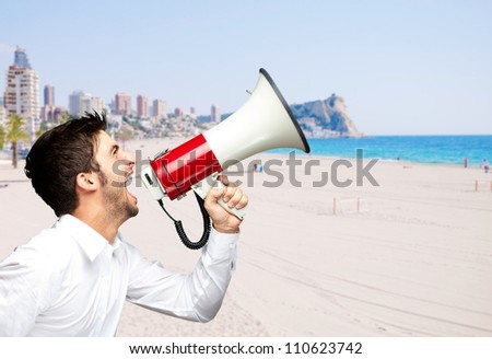 portrait of young man screaming with megaphone against a beach - stock photo