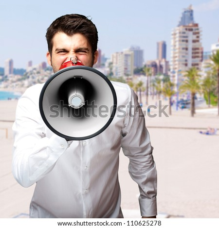portrait of young man screaming with megaphone against a beach