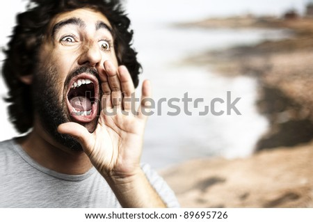 portrait of young man shouting against a beach background - stock photo