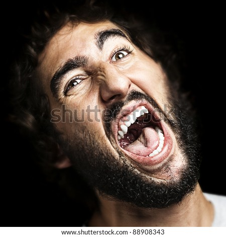 portrait of young man shouting against a black background - stock photo