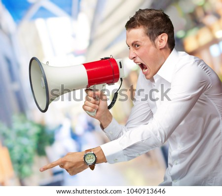 Portrait Of Young Man Shouting On Megaphone