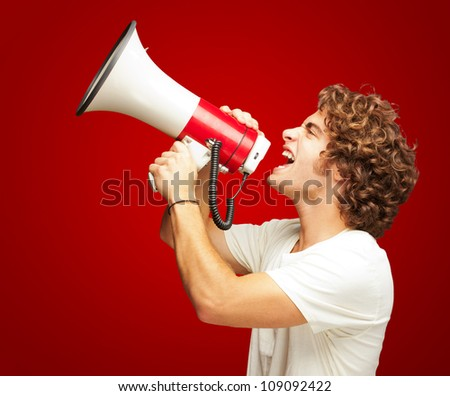 Portrait Of Young Man Shouting With A Megaphone Isolated On Red Background - stock photo