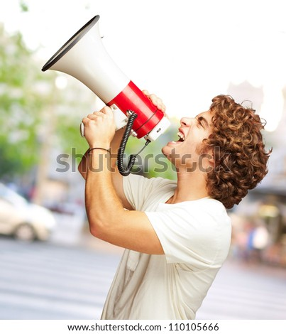 Portrait Of Young Man Shouting With A Megaphone, Outdoor - stock photo