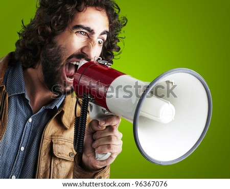 portrait of young man shouting with megaphone against a green background - stock photo