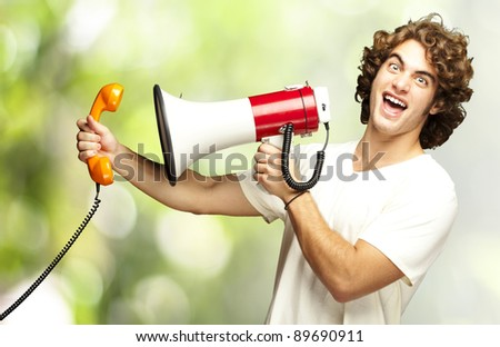 portrait of young man shouting with megaphone and talking on vintage telephone against a nature background
