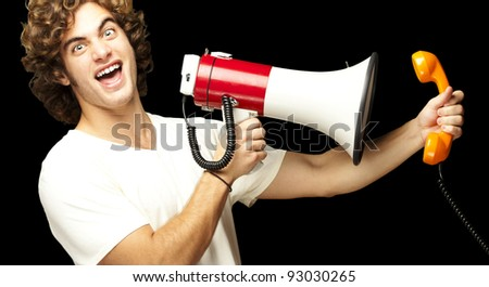 portrait of young man shouting with megaphone and talking on vintage telephone over background - stock photo