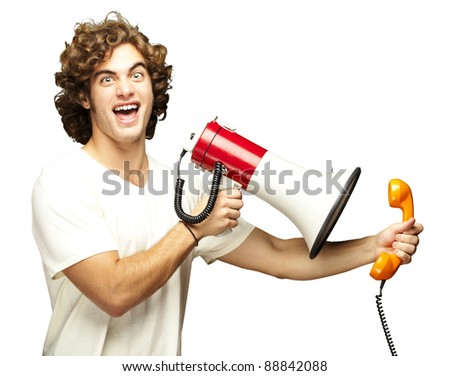 portrait of young man shouting with megaphone and talking on vintage telephone over white - stock photo