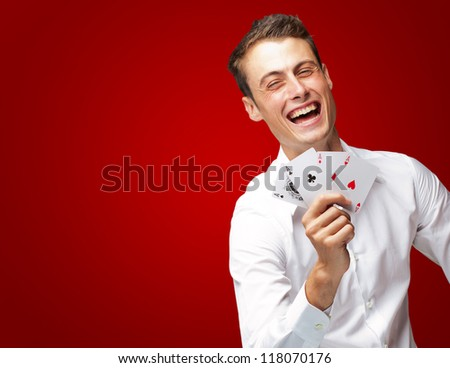 Portrait Of Young Man Showing Poker Cards On Red Background - stock photo