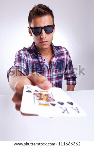 Portrait of young man showing poker pair of king and ace of clubs on gray background - stock photo
