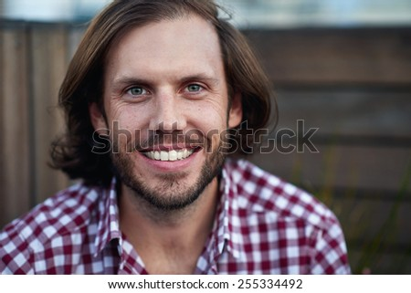 Portrait of young man sitting and smiling outdoors - stock photo