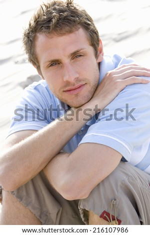 Portrait of young man sitting at beach - stock photo