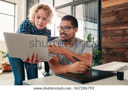 Portrait of young man sitting at his desk pointing at laptop in hands of a female colleague, male graphic designer help a female coworker in office. - stock photo