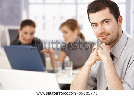 Portrait of young man sitting at meeting table, women working in the background.? - stock photo