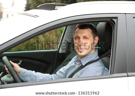 Portrait of young man sitting in the car - stock photo