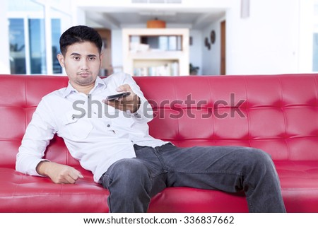 Portrait of young man sitting on sofa while watching tv and looks bored, using smartphone as remote control - stock photo