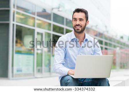 Portrait of young man sitting outside with laptop. He's looking away. Shallow depth of field with focus on young man sitting with laptop.