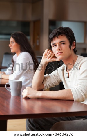 Portrait of young man sitting with a cup of tea while looking at the camera - stock photo