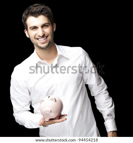 portrait of young man smiling and holding a piggy bank against a black background - stock photo