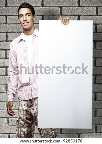 portrait of young man smiling and showing a banner against a bricks wall - stock photo