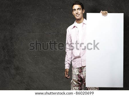 portrait of young man smiling and showing a banner against a grunge wall - stock photo