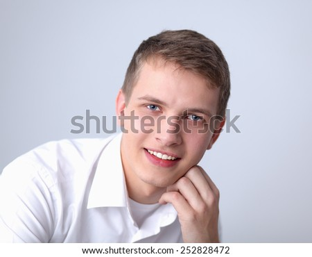 Portrait of young man smiling sitting on gray background - stock photo