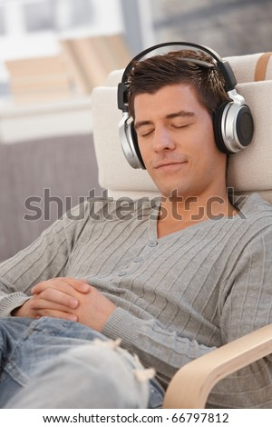 Portrait of young man smiling with eyes closed, listening to music via headphones at home.? - stock photo