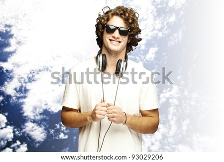 portrait of young man smiling with headphones against a cloudy sky background