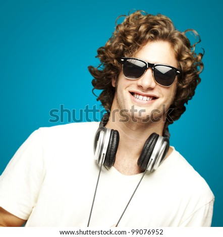 portrait of young man smiling with headphones over blue background
