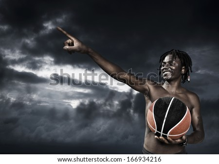 Portrait of young man street basket player against a dark sky - stock photo