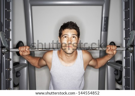Portrait of young man struggling to lift weights at gym - stock photo