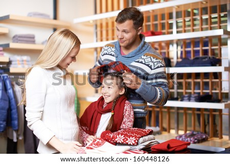 Portrait of young man trying cap on his daughter with pretty female near by - stock photo