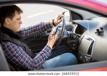 Portrait of young man typing message while driving a car - stock photo